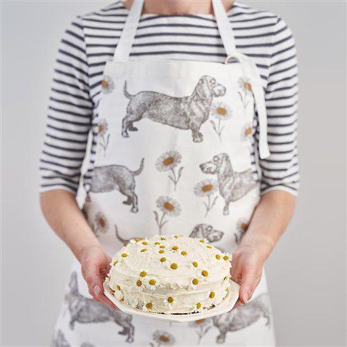 Vrouw draagt Teckel en Madeliefjes keukenschort en laat taart zien
